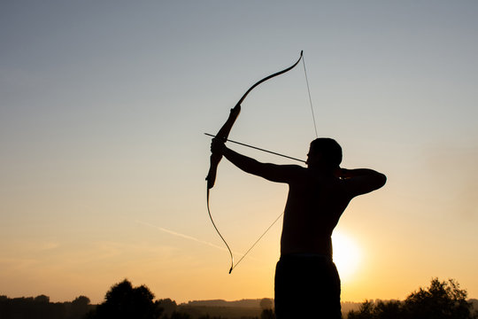 Silhouette of a man with an ancient weapon bow and arrow on a background of sky and sunset