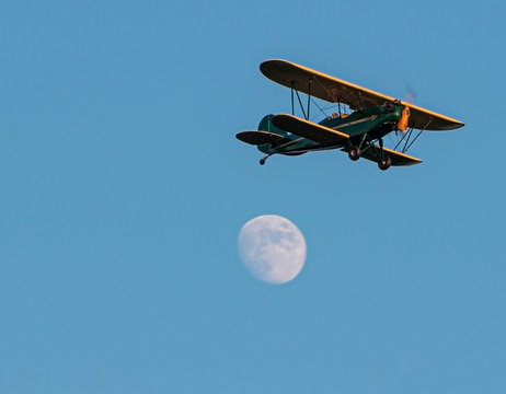 Green antique bi plane with yellow trim flying past full moon