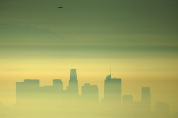 Downtown Los Angeles and an airplane are seen through the morning marine layer in Los Angeles
