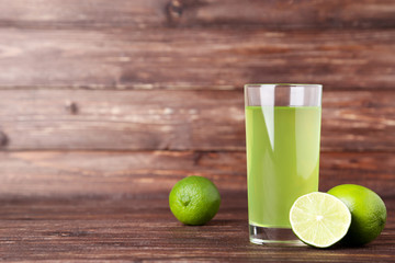 Wall Mural - Lime juice in glass on brown wooden table