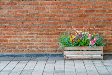 a basket of flowers was decorated in front of vintage red brick wall background