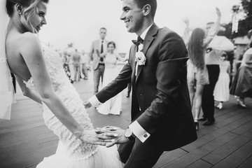 Stylish happy bride and groom having fun and dancing at wedding reception. Gorgeous wedding couple of newlyweds having first dance on background of guests