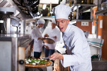 Happy surprised chef getting pizza out of oven