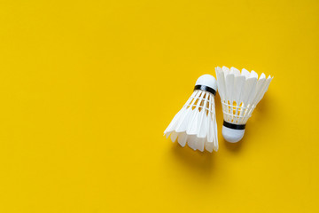 close up top view of white shuttlecocks on yellow color background with copy space for design,show content and promote banner for  sport concept