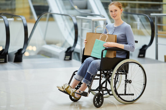 Portrait of young disabled woman sitting in wheelchair with shopping bags and smiling at camera in the modern shopping mall