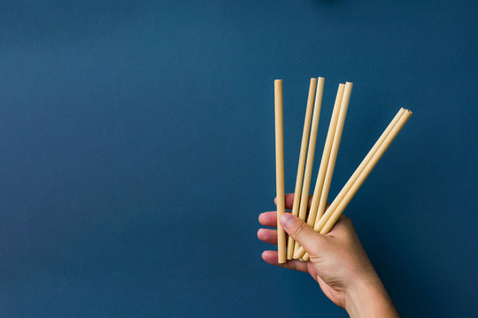 bamboo straws in a hand in blue background