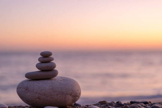Perfect balance of stack of pebbles at seaside towards sunset. Concept of balance, harmony and meditation. Helping or supporting someone for growing or going higher up.