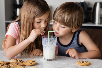 Siblings blowing bubbles in a glass of milk with straws