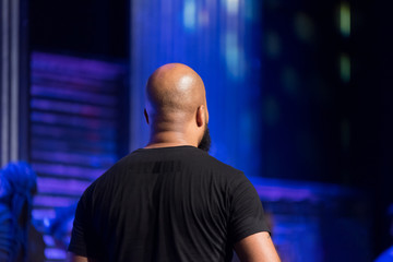 Indoor Portrait of a Bald African American Man with a Beard Facing Away from the Camera