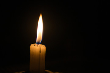 Close up image of a candle burning in a dark room