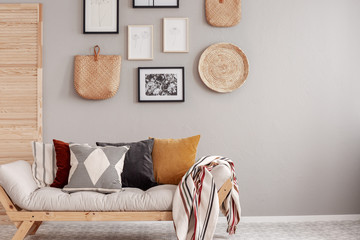 Colorful pillows and blanket on scandinavian futon sofa in natural living room interior Fototapete