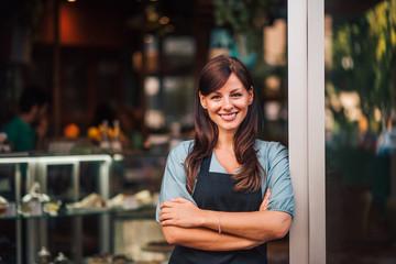 Foto op Canvas Restaurant Portrait of a beautiful positive waitress standing in the doorway