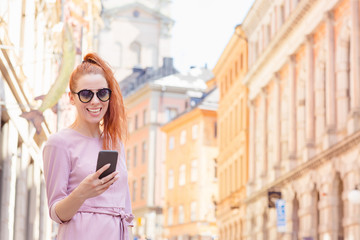 Beautiful woman standing on the street and using her mobile phone