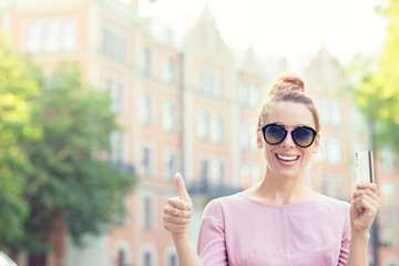 Cheerful excited young woman with credit card giving thumb up standing outdoors