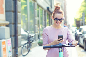 Happy woman in sunglasses using smartphone and renting modern electric scooter with an application