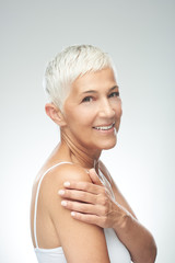 Beautiful smiling senior woman with short gray hair posing in front of gray background. Beauty...