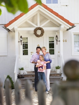 Family with baby standing in front of house