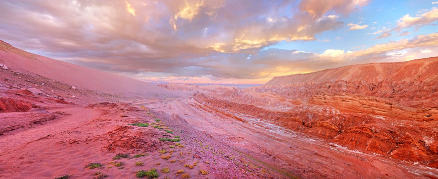 Panoramic view of the Mars Valley near San Pedro de Atacama against a warm and colorful sunset sky above volcanoes.