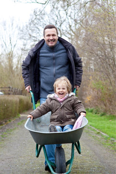 Germany, Father pushing daughter on wheel barrow, smiling