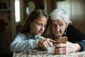 Granny and granddaughter. A cute little girl shows her grandmother a smartphone.