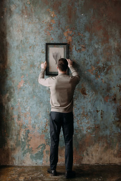 Man hanging painting on wall