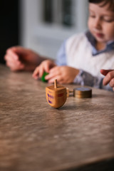 Hanukkah: Boy And Parent Playing Dreidel