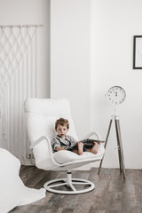 Little boy reading sitting in armchair