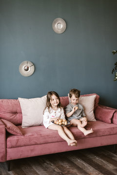 Little children sitting on sofa with food