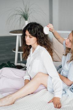 Sensual women brushing hair on bed