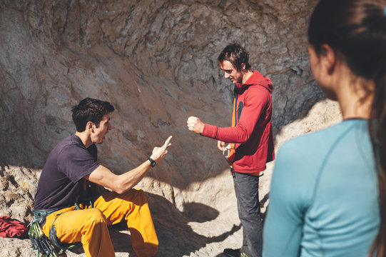 Two male climbers play stone, paper and scissors on rocky scenery