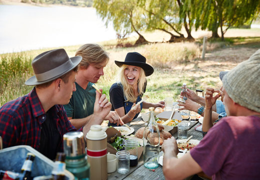 Group of millennial friends having a picnic in the park together