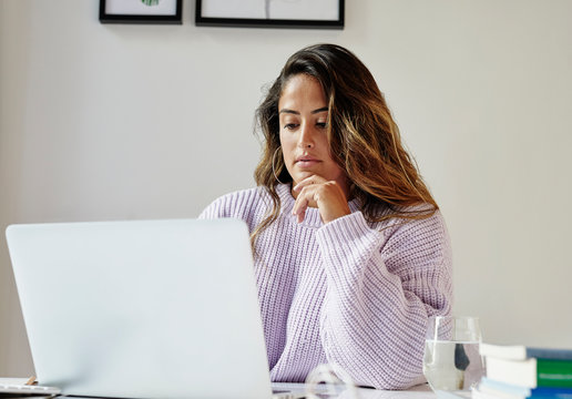 Young professional woman working at a desk in her home office.