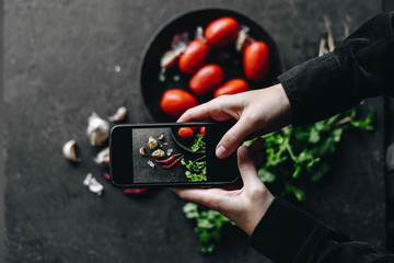 Crop hands taking pictures of spices and tomatoes