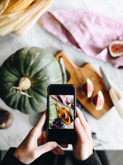 Crop hands taking picture of fig and pumpkin