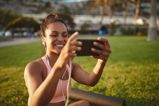 Smiling young woman taking a selfie after yoga practice outside