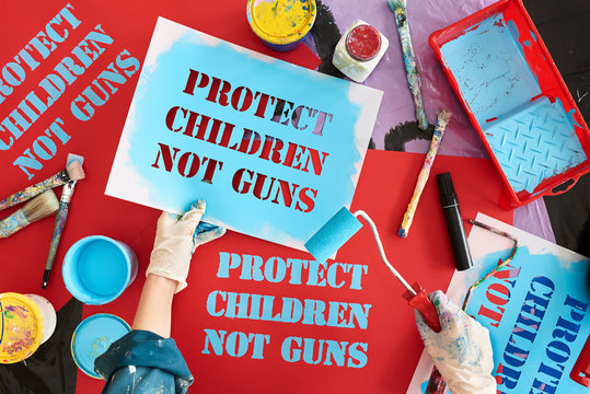 Passionate parent painting protest signs for gun control march