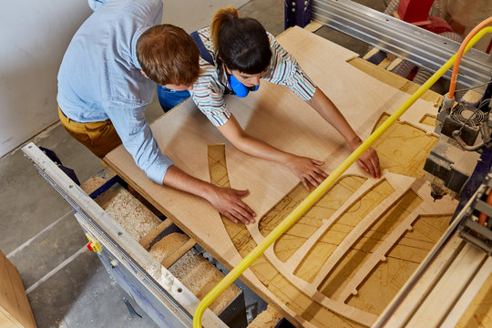 High angle view of teacher assisting student in using laser cutter on wood at university