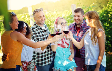 Group of friends toasting and drinking red wine and having fun outdoors - Wine tasting experience at farmhouse winery countryside
