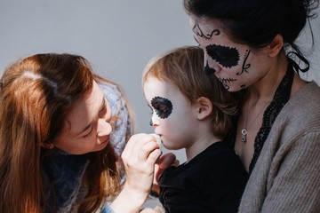 Make up artist creating halloween face art on the boy sitting on his mother's knees