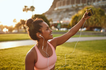 Smiling woman taking selfies in a park after practicing yoga