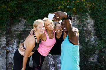 Senior friends taking selfie outdoors after workout.