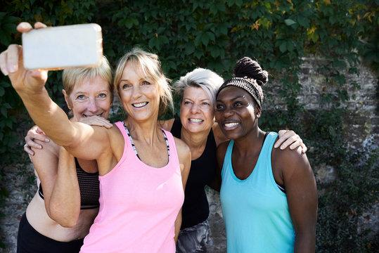 Senior ladies taking selfie outdoors after workout.
