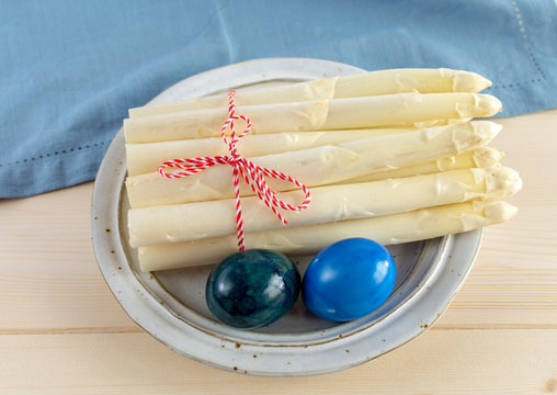 New harvest of white asparagus and colored Easter eggs, high quality raw asparagus in spring season, ingredients for Easter dinner
