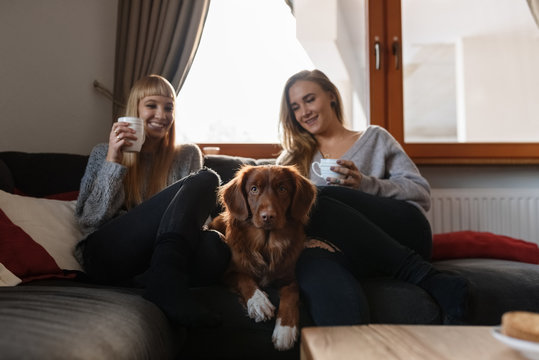 Smiling women with beverages and dog
