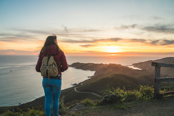 Girl solo traveler watching a beautiful sunset over the Pacific Ocean on top of a hill Wall mural