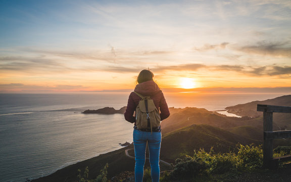 Girl traveler watching a beautiful sunset over the Pacific Ocean on top of a hill