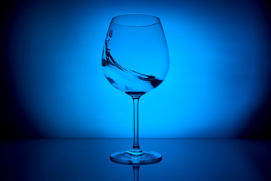 wine glass with water splash on the lighting blue background