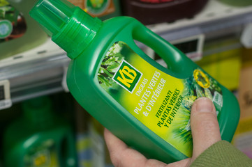 closeup of fertilizer bottle from KB brand  in hand  at Super U supermarket