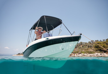 From below elderly man in hat and sunglasses sailing on black and white boat in calm turquoise water of Halkidiki, Greece