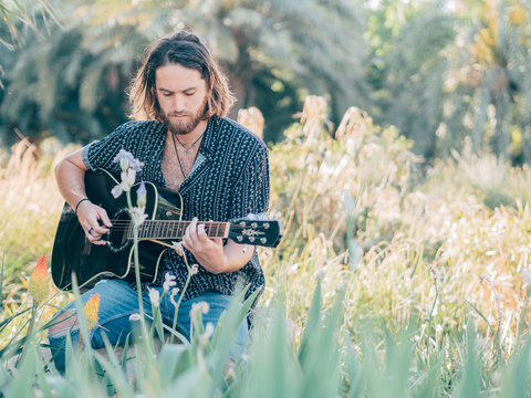 Pensive bearded hipster man sitting in meadow playing guitar